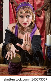 Mysterious female fortune teller showing an evil eye in palm