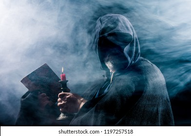 a mysterious figure holds a book and a candle in his hands