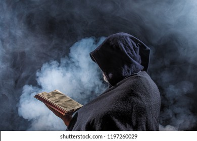 a mysterious figure holds a book in his hands