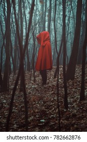 Mysterious figure in misty forest. Red hooded