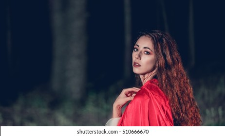 mysterious girl in a red cloak in a dark forest