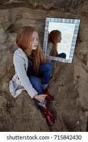 Mysterious girl redhead girl  watch mirrors in the nature. Autumn concept