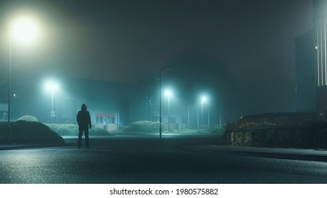 A mysterious hooded man standing in a street on an industrial estate looking at buildings on a misty winters night.         - Shutterstock ID 1980575882