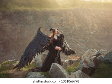 mysterious lady in black light lace dress with long train, girl with open leg, dark horned angel from heaven, messenger of death with large wings on edge with closed eyes in sun rays. Art photography