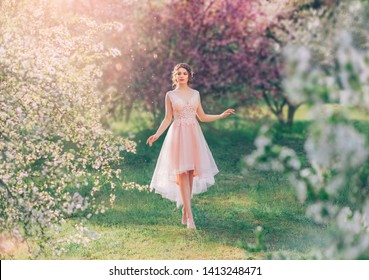 mysterious lady with dark gathered hair in a light delicate peach dress walks in the blooming garden, the spring fairy touches her possessions, the fairy-tale elf like a doll on the grass barefoot