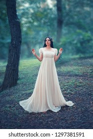 Mysterious lady in a white vintage dress, lost in the woods. Black long hair is decorated with a golden laurel wreath, like that of the Greek Goddess. Creative, artistic colors