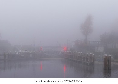 Mysterious landscape with sluice in the mist with looming red lights.