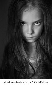Mysterious little girl with long hair, black and white photography.