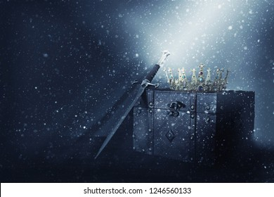 mysterious and magical image of old crown, wooden chest and sword over gothic black background. Medieval period concept