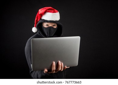 Mysterious male santa hacker holding laptop computer, anonymous man on black background, ransomware cyber attack and internet security on Christmas holiday concepts