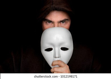 Mysterious man in black hiding his face behind white mask - anonymous concept