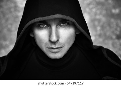 Mysterious Man in Black Hoodie. Sexy Hero Guy. Pastor or Wizard in Robe. Assassin or Witcher with Strong Face Expression in Cloak. Dark Magician Black and White Photo. Fantasy Book Cover Concept.