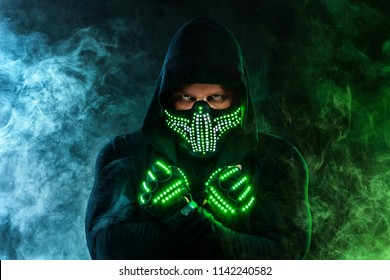 Mysterious man in black wear, neon mask and gloves. Character pastor or wizard in robe from the future. Assassin with strong face expression. Fantasy book or computer game cover concept.