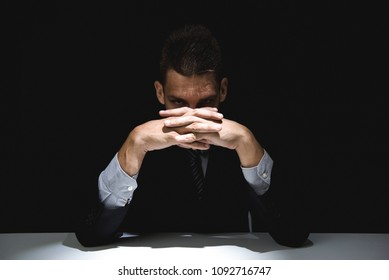 Mysterious man in formal suit with clasped hands at the table, staring at camera in dark shadow