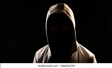 Mysterious man with hoodie on the black background