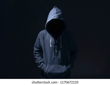 Mysterious man with hoodie in silhouette on black background. committed a crime concept.