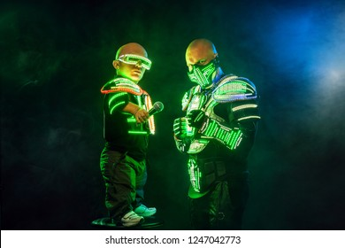 Mysterious man and midget in black wear, neon mask and gloves. Character pastors or wizards in robe from the future. Assassin with strong face expression. Fantasy book or computer game cover concept.