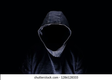 Mysterious man silhouette with darkened face, no visible face, in blue hoodie on dark background