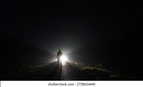 A mysterious man silhouetted against car headlights on a country road on a misty winters night