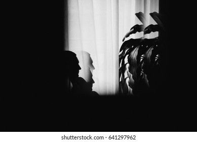 Mysterious man sitting with shadows by the window. Dark background