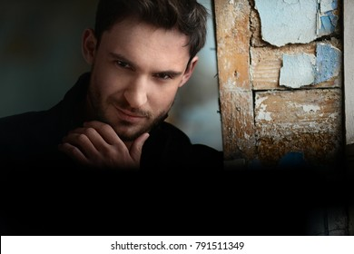 Mysterious man with a sneaky look. Handsome man with a confident look. Sexy and smart man in a suit with beautiful eyes. Hot looking businessman on a dark romantic background.