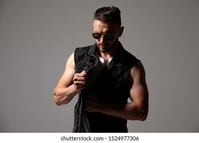 Mysterious man taking something out of his jeans vest while wearing sunglasses and standing on gray studio background