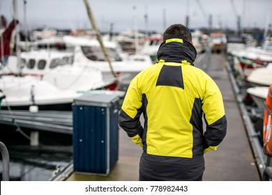 Mysterious man in yellow jacket walks on the pier between white boats on the gray sky background. Shoot from the back. Low aperture closeup photo. Horizontal.