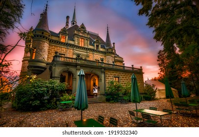Mysterious mansion at sunset in Halloween. Manor with cafe tables at sunset. Sunset manor. Sunset mansion house