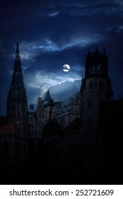 Mysterious medieval castle and the cathedral church at night on a background of the full moon