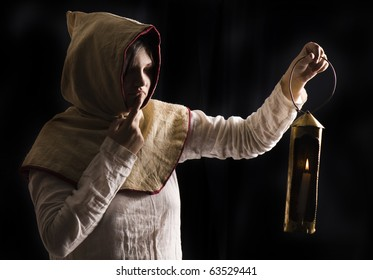 mysterious medieval woman holding a burning lantern