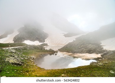 Mysterious mountain lake among fog in the Caucasus in summer.