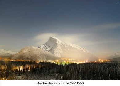 Mysterious night look of Mt. Rundle, covered with snow and Fairmont Banff Springs hotel in sight. Famous landmark in Banff.