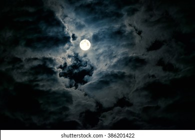 Mysterious night sky with full moon. Concept of a spooky theme and mystery. Dramatic clouds in the moonlight from full moon.