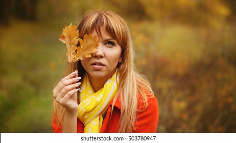 Mysterious portrait of a girl hiding her face behind autumn leaves.