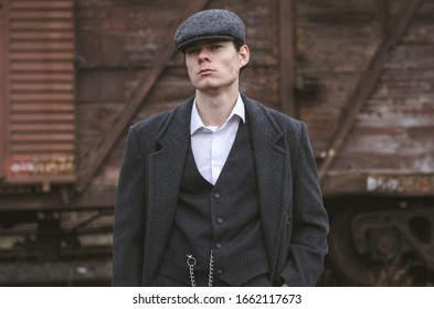 Mysterious portrait of retro 1920s english gangster with flat cap on railway station.
