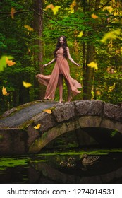 Mysterious pretty girl in a long dress in the wind. The leaves in a forest are falling. A background of trees. Art photo