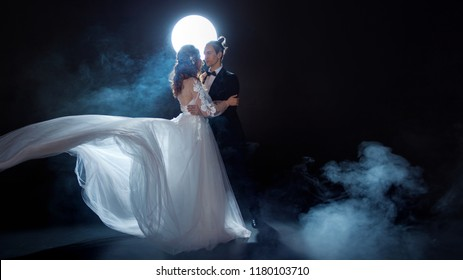 Mysterious and romantic meeting, the bride and groom under the moon. Hugs together. Man and woman, wedding dress. Dark background