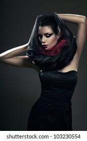 mysterious sexy woman in black hood in dark