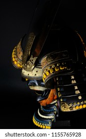 Mysterious side view of a historic samurai helmet with mask in front of a black background and dim lighting