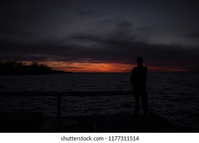 Mysterious silhouette man at night on pier