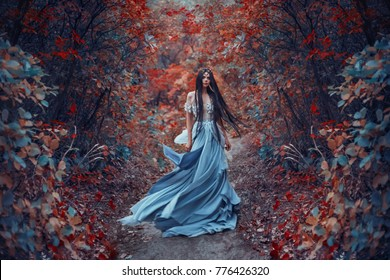 Mysterious sorceress elf woman beautiful blue dress. long hair dress  fluttering fly wind. Background bright autumn fairy red mystic forest trees. Gothic Art Photography. Young nymph nature goddess
