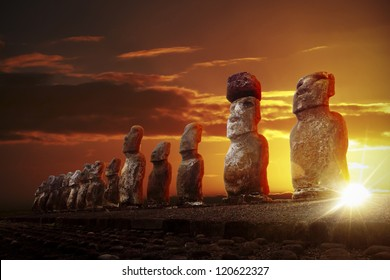 Mysterious stone statues at dramatic orange sunrise in Easter Island