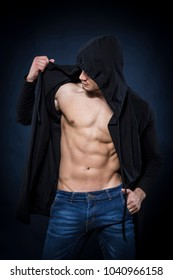 Mysterious strong man with black sweatshirt on dark background