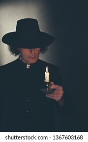 Mysterious victorian priest in black coat and hat holding candlestick.