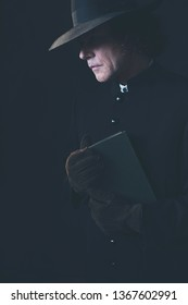 Mysterious victorian priest in hat holding book.