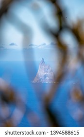 Mysterious view of Ball's Pyramid Rock off the coast of Lord Howe Island, New South Wales, Australia, seen through tree branches on the summit of Mount Gower, Lord Howe Island's highest mountain.