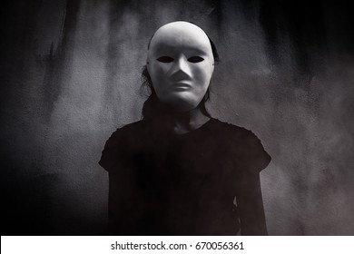 Mysterious woman in black wearing white mask hidden behind the dark,Scary background for book cover