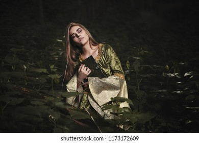 Mysterious woman with eyes closed in dark fairy forest. Fantasy story