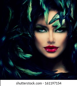 Mysterious Woman Portrait. Beautiful Model Woman Face Closeup. Feathers Hairstyle. Darkness.