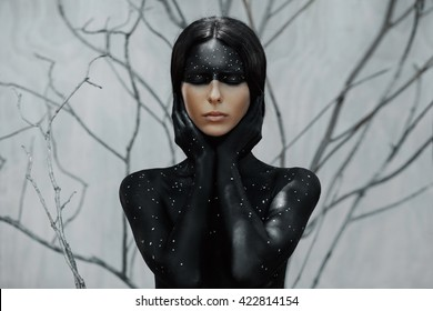 Mysterious woman portrait with branches background. Body art with moon and stars.